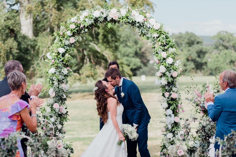 Les mariés s'embrassent sous l'arche fleurie
