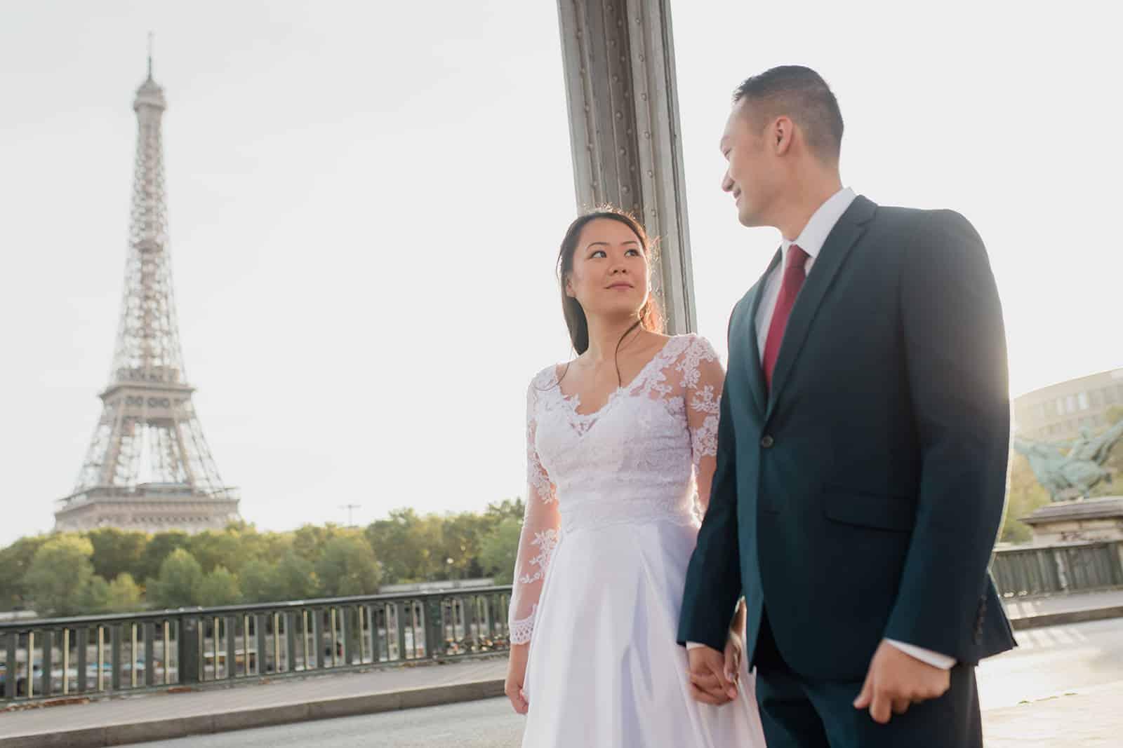 Couple main dans la main devant la tour eiffel